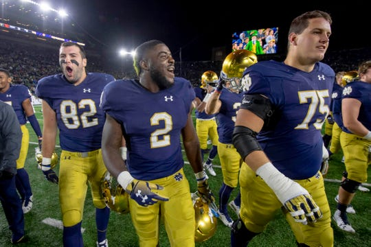 Fighting Irish tight end Nic Weishar (82) , running back Dexter Williams (2) and offensive lineman Josh Lugg (75) celebrate after Notre Dame defeated the Stanford Cardinal at Notre Dame Stadium.