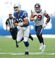 Indianapolis Colts quarterback Andrew Luck (12) runs away from Houston Texans defensive end J.J. Watt (99) in the second half of their game on Sunday, Sept. 30, 2018. The Indianapolis Colts lost 37-34 in overtime to the Houston Texans.