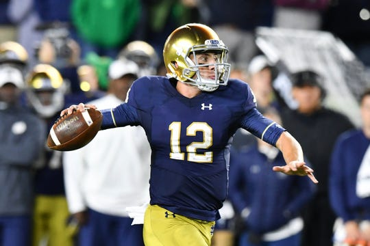 Notre Dame Fighting Irish quarterback Ian Book (12) throws for a touchdown in the second quarter against the Stanford Cardinal at Notre Dame Stadium.