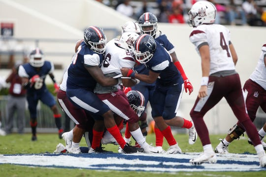 JSU defenders Malik Hammer, left and Keontre Hampton, right pull down an Alabama A&M running back.
