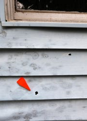 An evidence marker noting an apparent bullet hole in the siding of a duplex.