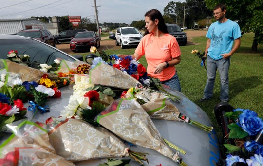 Hanna Hux, left, places flowers on the patrol car of her childhood friend, Brookhaven police officer James White, in Brookhaven, Miss., Sunday, Sept. 30, 2018.
