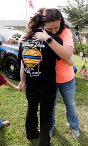 Hanna Hux, right, hugs a friend of Brookhaven, Miss., slain Patrolman James White, Sunday, Sept. 30, 2018, by White's vehicle, parked on the front of the Brookhaven Police Station.
