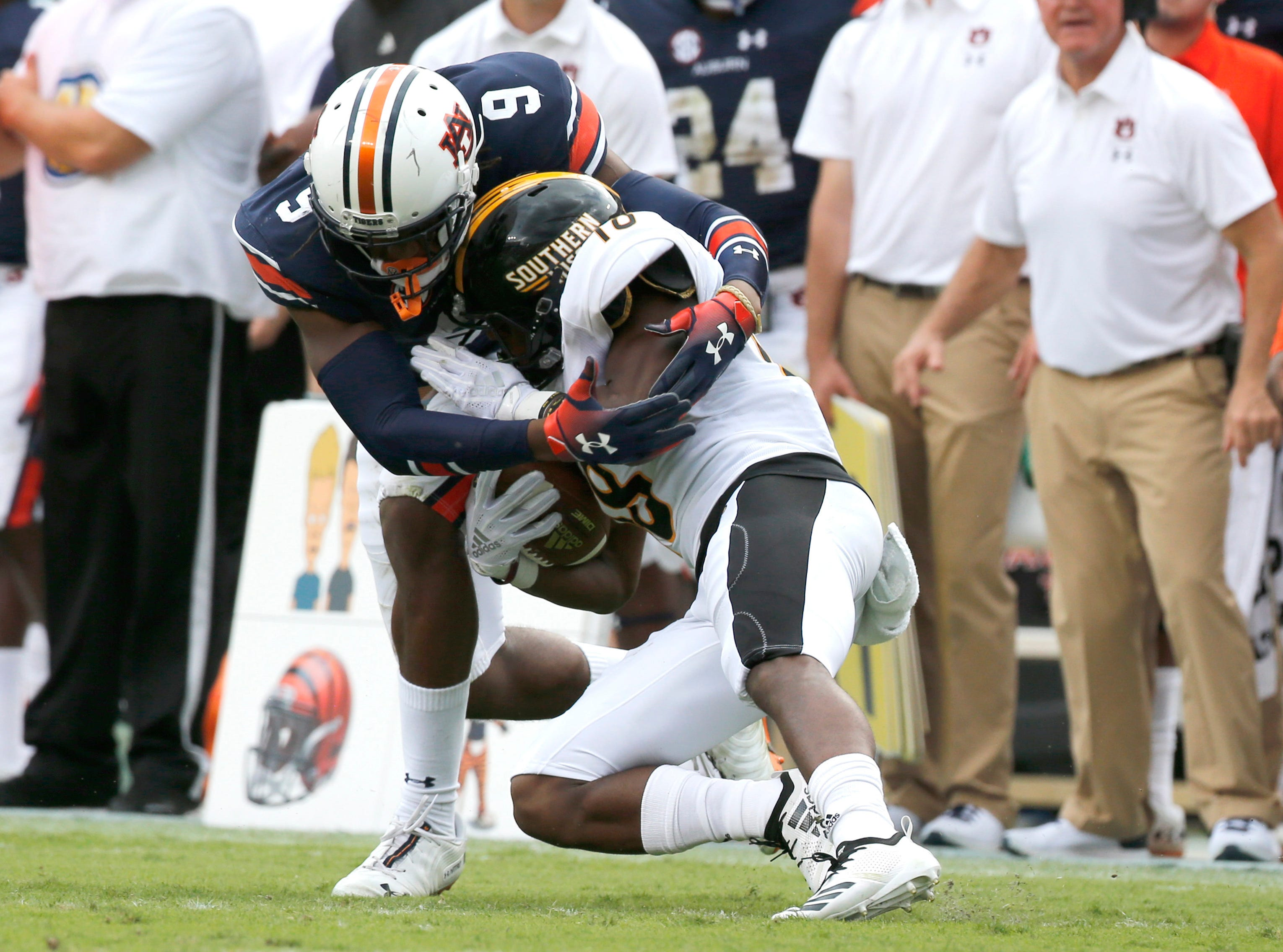 Sep 29, 2018; Auburn, AL, USA; Southern Miss Golden Eagles received er De'Michael Harris (18) is tackled by Auburn Tigers defensive back Jamien Sherwood (9) during the first quarter at Jordan-Hare Stadium. Mandatory Credit: John Reed-USA TODAY Sports