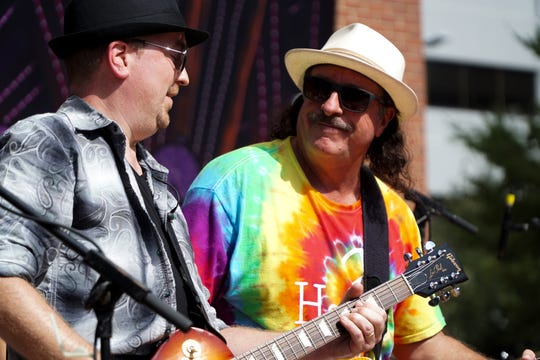 Chuck Nelson, right, smiles during a performance by Soul Sacrifice, a Santana tribute band, during the 19th annual HoLa Festival in Market Square on Sunday.