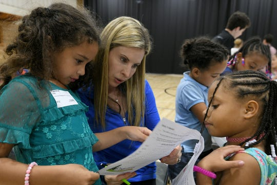 Jennifer Grace works with Tianna Edge, left, and children at Cedarbrook Outreach program at West Park Baptist Church Tuesday, September 25, 2018.