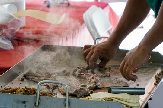 Alvaro Garibay prepares various meats for tacos at the 19th annual HoLa Festival in downtown Knoxville on Sunday, September 30.
