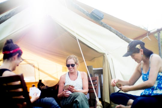 From left, Maggie Moroff, of New York, Dede Lipp, of California, and May Lee, also of New York, play cards outside their safari tent at Under Canvas Great Smoky Mountains in Pigeon Forge, Tenn., on Saturday, Sept. 29, 2018. Under Canvas is a glamping retreat where campers rent their own tents and have access to showers and meals.