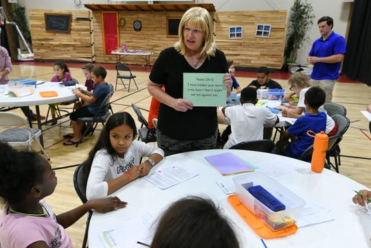 Debra Keller helping students with the Bible memory verse game during Cedarbrook Outreach program at West Park Baptist Church Tuesday, September 25, 2018.