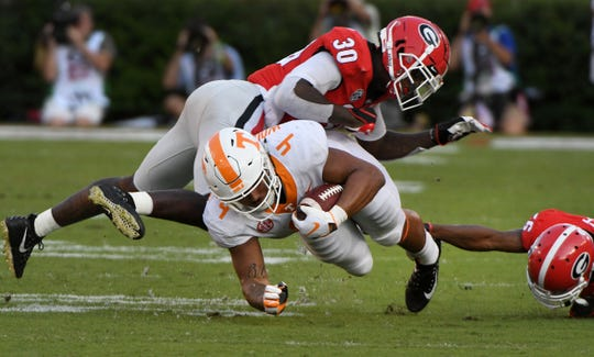 Tennessee tight end Dominick Wood-Anderson (4) is tackled by Georgia defensive back Divaad Wilson (16) and linebacker Tae Crowder (30) during second half action Saturday, September 29, 2018 at Sanford Stadium in Athens, GA.