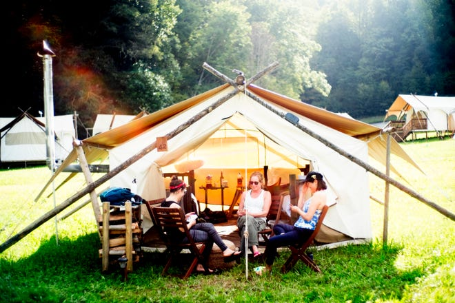 From left, Maggie Moroff, of New York, Dede Lipp, of California, and May Lee, also of New York, play cards outside their safari tent at Under Canvas Great Smoky Mountains in Pigeon Forge, Tenn., on Saturday, Sept. 29, 2018. Under Canvas is a glamping retreat where campers rent their own tents and have access to showers and meals. The 182-acre site has 40 tents with plans to add more next year.