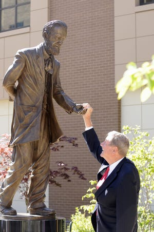 Thomas E. Brennan Sr., founder of Cooley Law School in Lansing, enjoys a playful moment with the new statute of Justice Thomas M. Cooley, June 26, 2012.