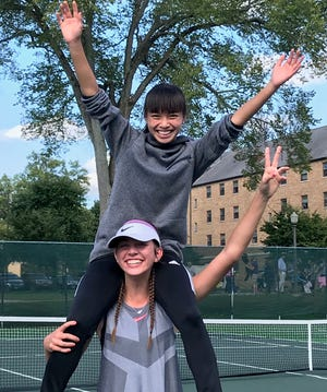 Lexington senior Abbey Dawson, at 6 feet a foot taller than her partner, puts freshman Gracie Pfieffer on her shoulders after they won the No. 1 doubles title in Saturday's Ohio Cardinal Conference tournament at the College of Wooster.