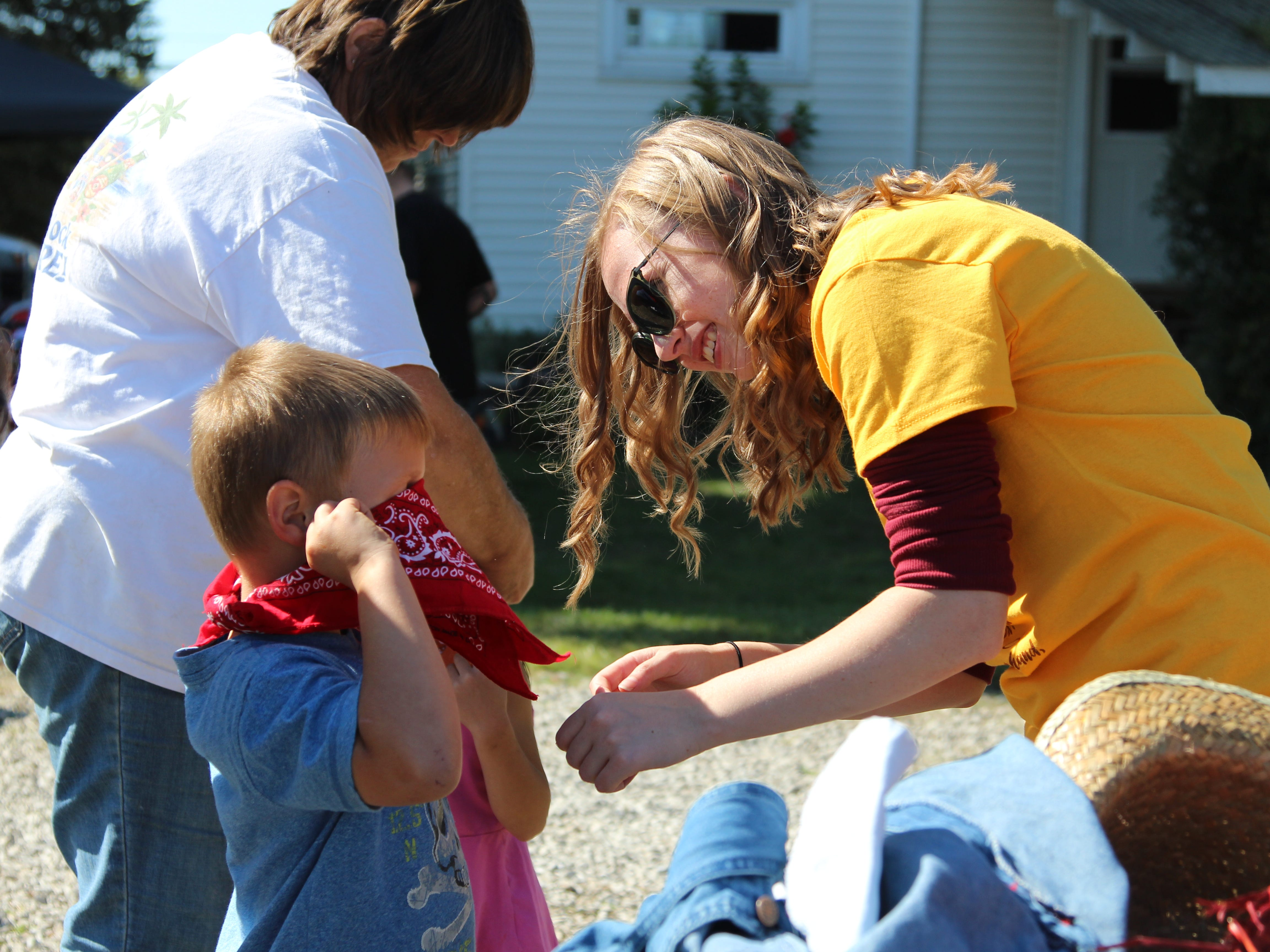 Alexis Teal, a volunteer at Applefest, helps Max Wilcox, 5, put on a bandana. Applefest, the annual fall festival at Lawrence Orchards just outside Marion, took place Saturday.