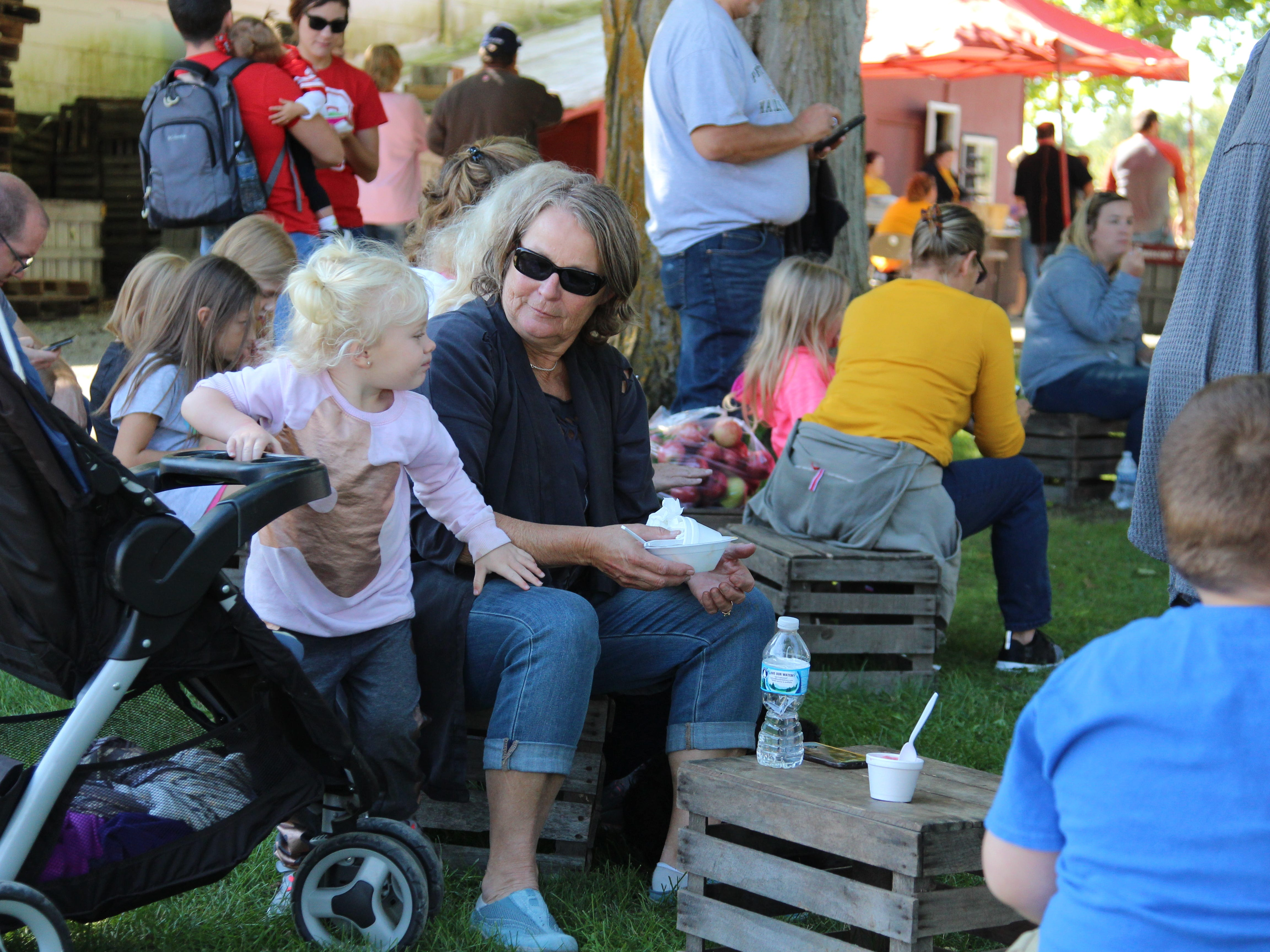 People eat and watch the gospel/bluegrass band Grail play at Applefest, which took place Saturday at Lawrence Orchards.