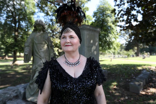 Cathi Johnson, dressed as and representing Marie Greenwood Warden, a Memphis Opera singer who died in 1954, poses for a portrait at the Elmwood Cemetery on Saturday.