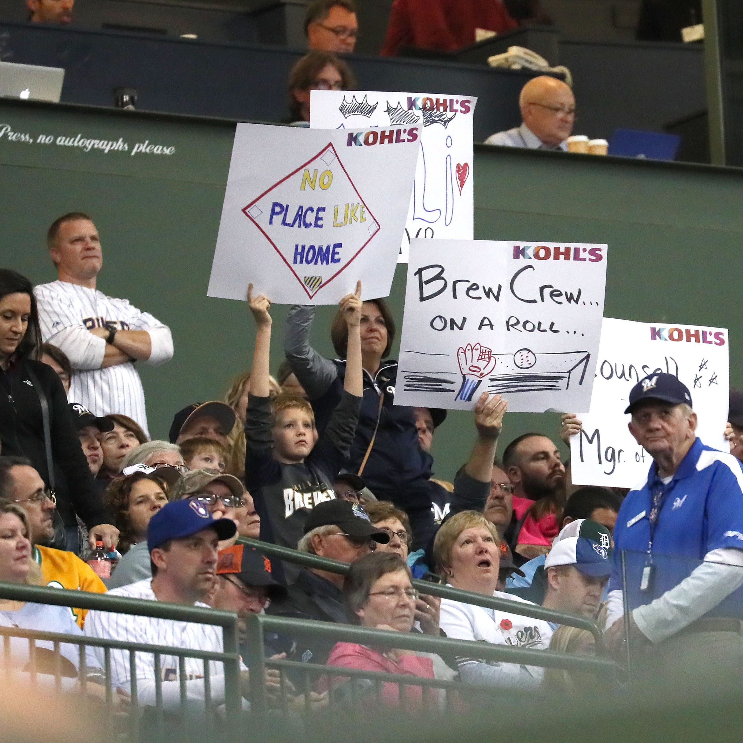 Fans hold signs high cheering the Brewers on at Miller Park where the Brewers played the Tigers looking for a regular playoff berth.