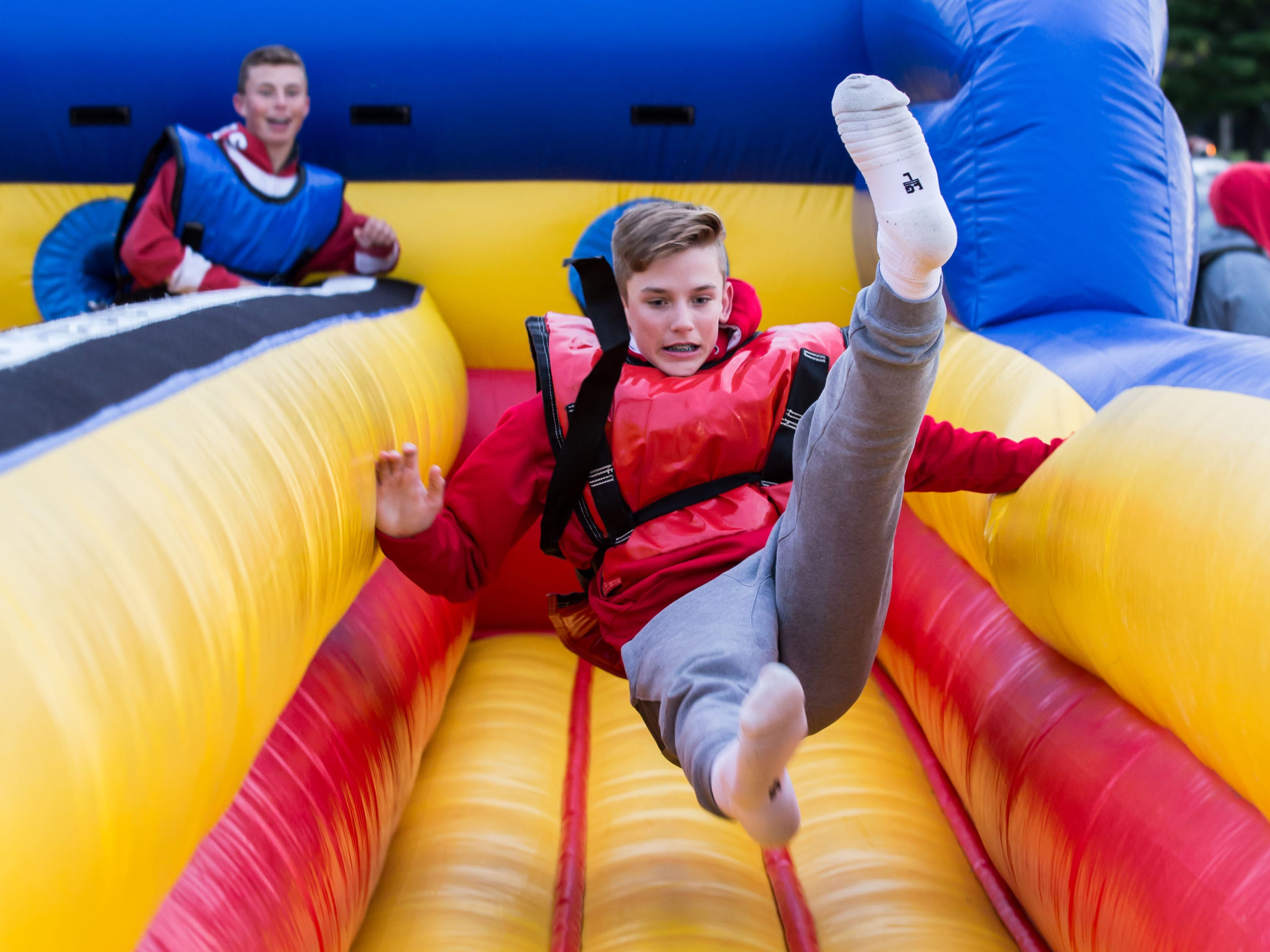 Freshman Josh Davies gets yanked backwards on the bungie game during the annual DECA Hawkfest event at Arrowhead High School in Hartland on Friday, Sept. 28, 2018. The event, which is free to attend, raises money for local charities via paid attractions, games, food and more.