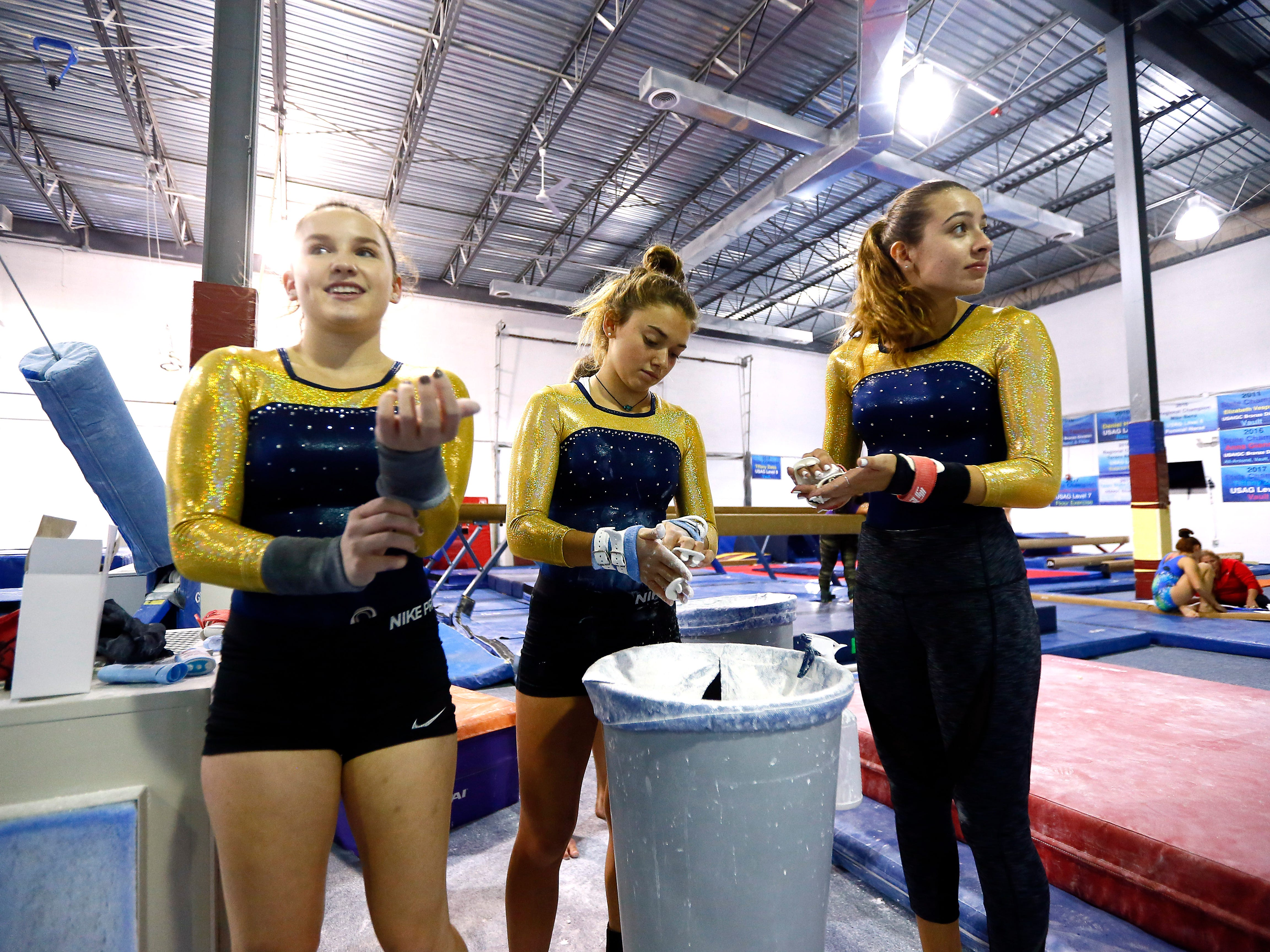 Roxbury High School junior Tiffany Zieba, l, junior  Ashley Miller and senior Nicole Arevalo chalk up during gymnastics practice at Northern Elite Gymnastics & Cheer in Flanders. Roxbury has just launched a girls gymnastics team.  September 25, 2018, Flanders, NJ