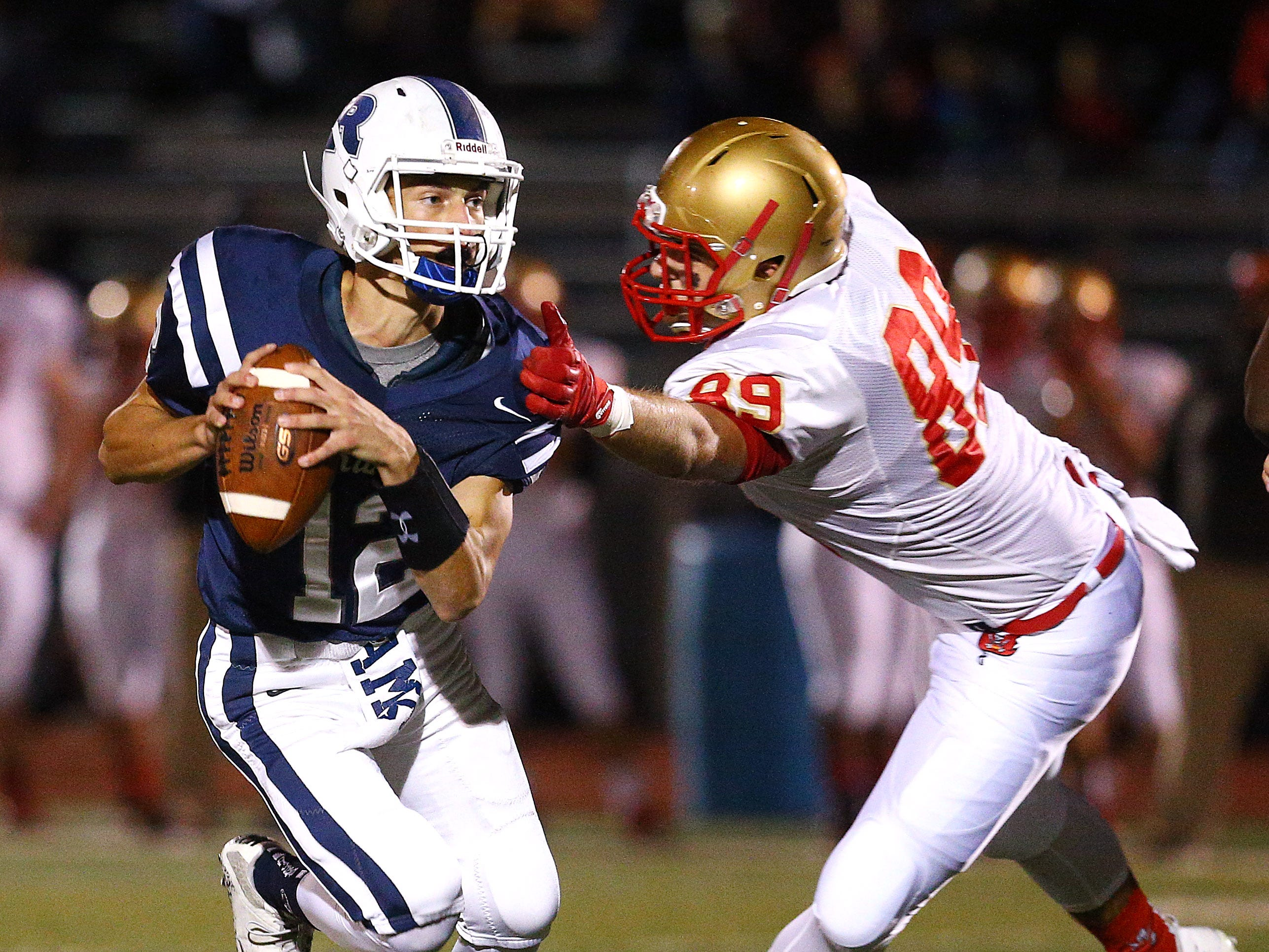 Randolph quarterback Anthony Sofia avoids a tackle by Mount Olive DT Chris Carpini during their SFC Freedom Blue Friday night football game. September 28, 2018, Randolph, NJ