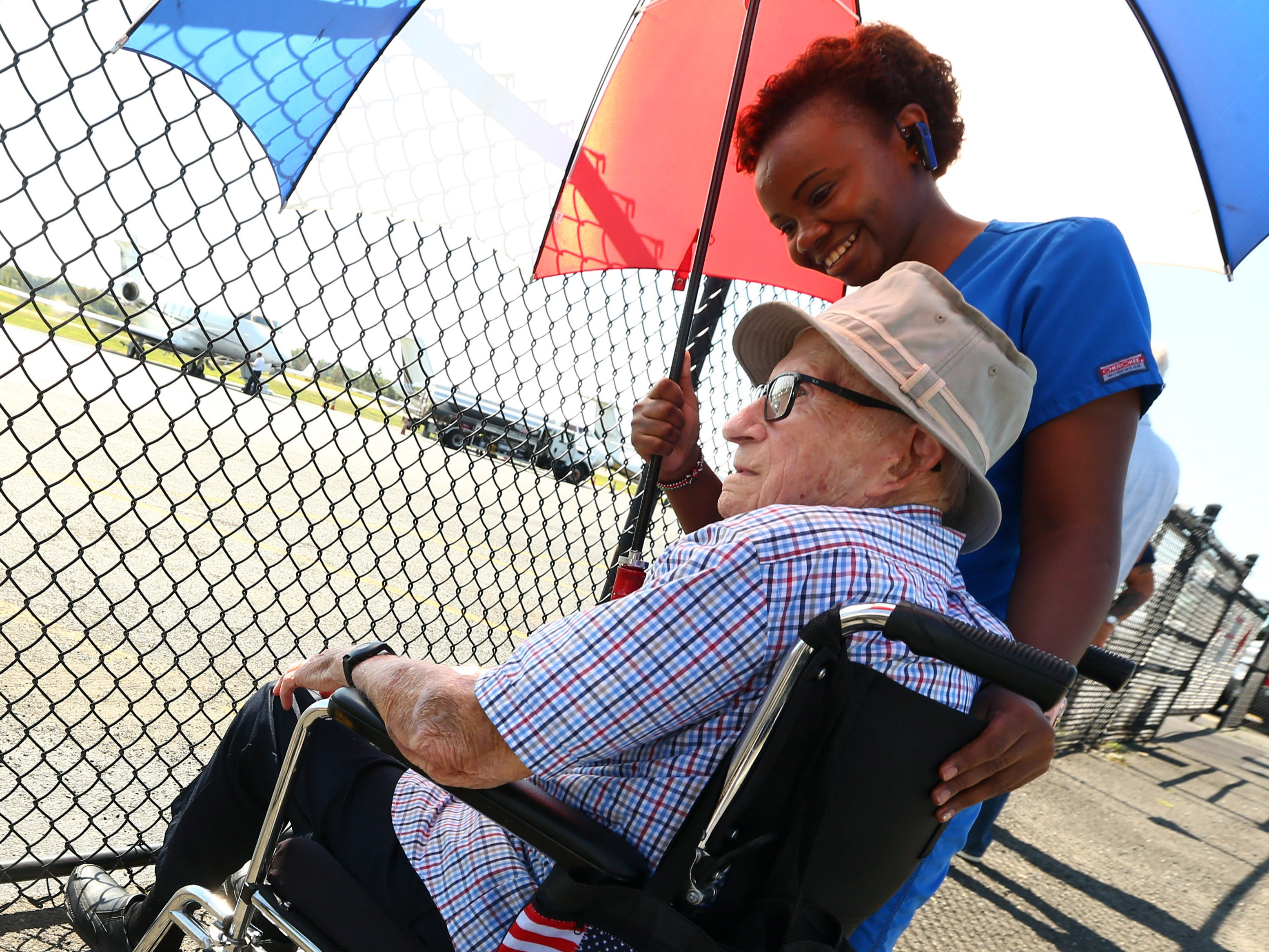 94-year-old Harry Kramer of Morristown and certified nursing assistant Rose Roberson wait for the arrival of  a B-25 Mitchell bomber, the type of plane Kramer flew in WWII. Four fighters flew into Morristown Municipal Airport as part of the Collings FoundationÕs Wings of Freedom Tour. September 4, 2018, Hanover, NJ