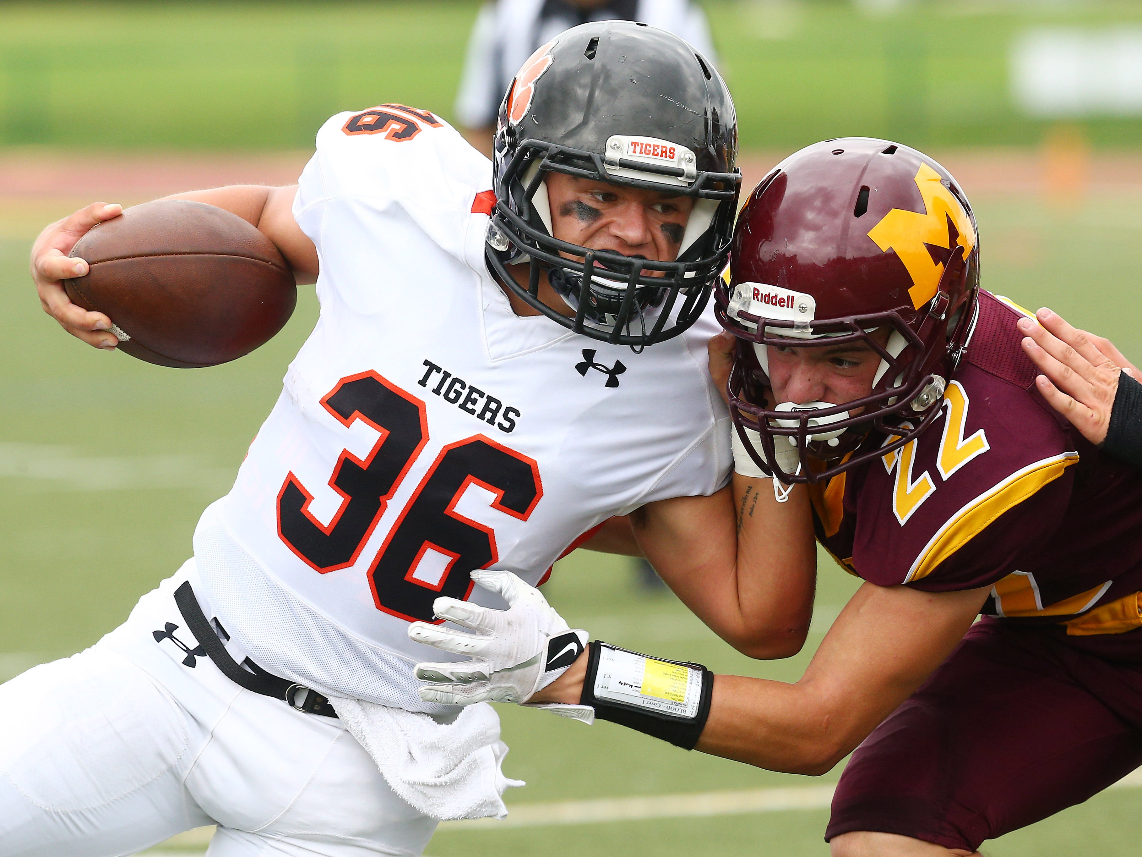 Hackettstown running back Tim Ervey is tacked by Madison's Vincent Costa in an American White Saturday football game. September 15, 2018, Madison, NJ