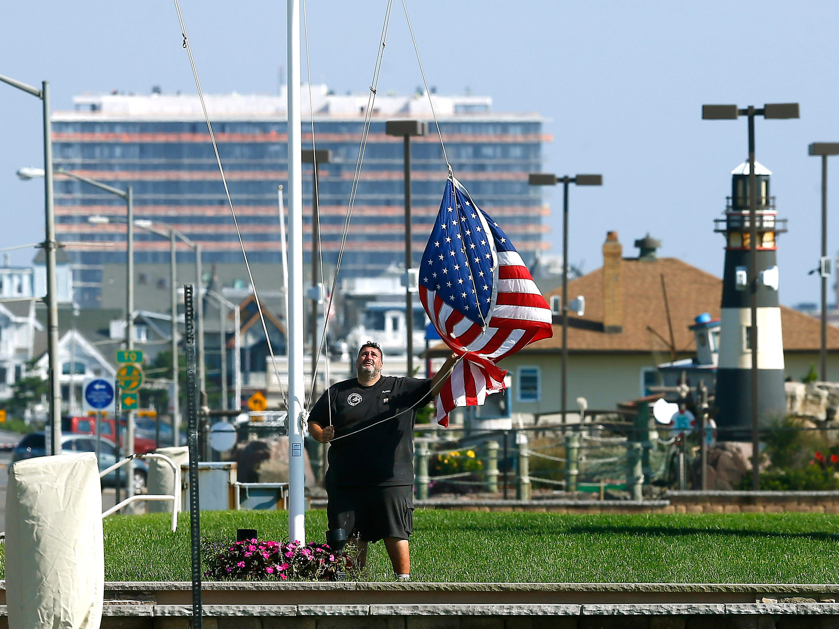 A man raises the American flag Wednesday morning at the Bill Nunnally Lifeguard Tower on Bradley Beach. Summer shore guide. September 19, 2018, Bradley Beach, NJ
