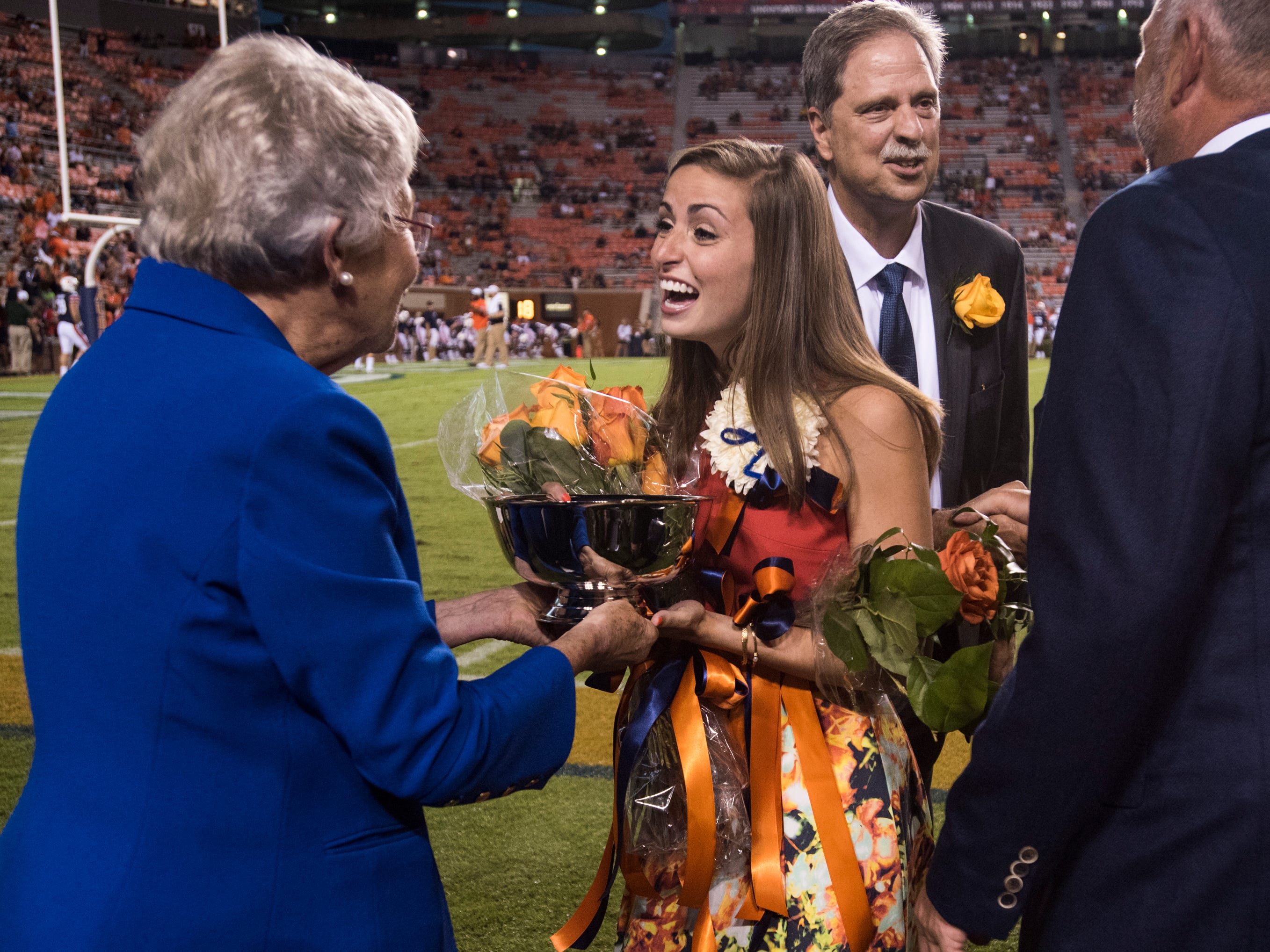 Alabama Gov. Kay Ivey presents Sadie Argo with her trophy after being announced homecoming queen at Jordan-Hare Stadium in Auburn, Ala., on Saturday, Sept. 29, 2018. Auburn defeated  Southern Miss 24-13.