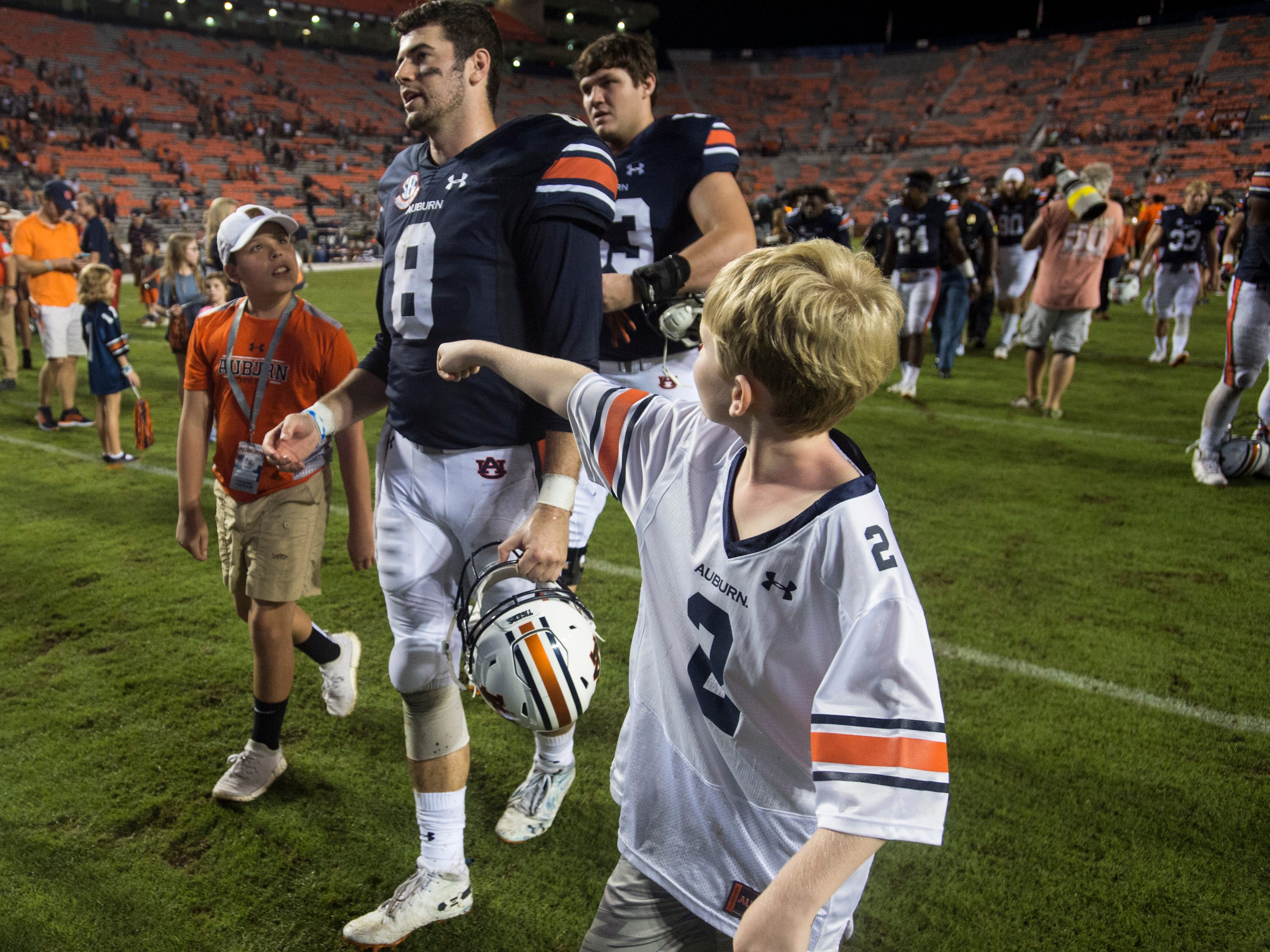 Auburn's Jarrett Stidham (8) is escorted by a couple of young fans as he walks off the field at Jordan-Hare Stadium in Auburn, Ala., on Saturday, Sept. 29, 2018. Auburn defeated  Southern Miss 24-13.