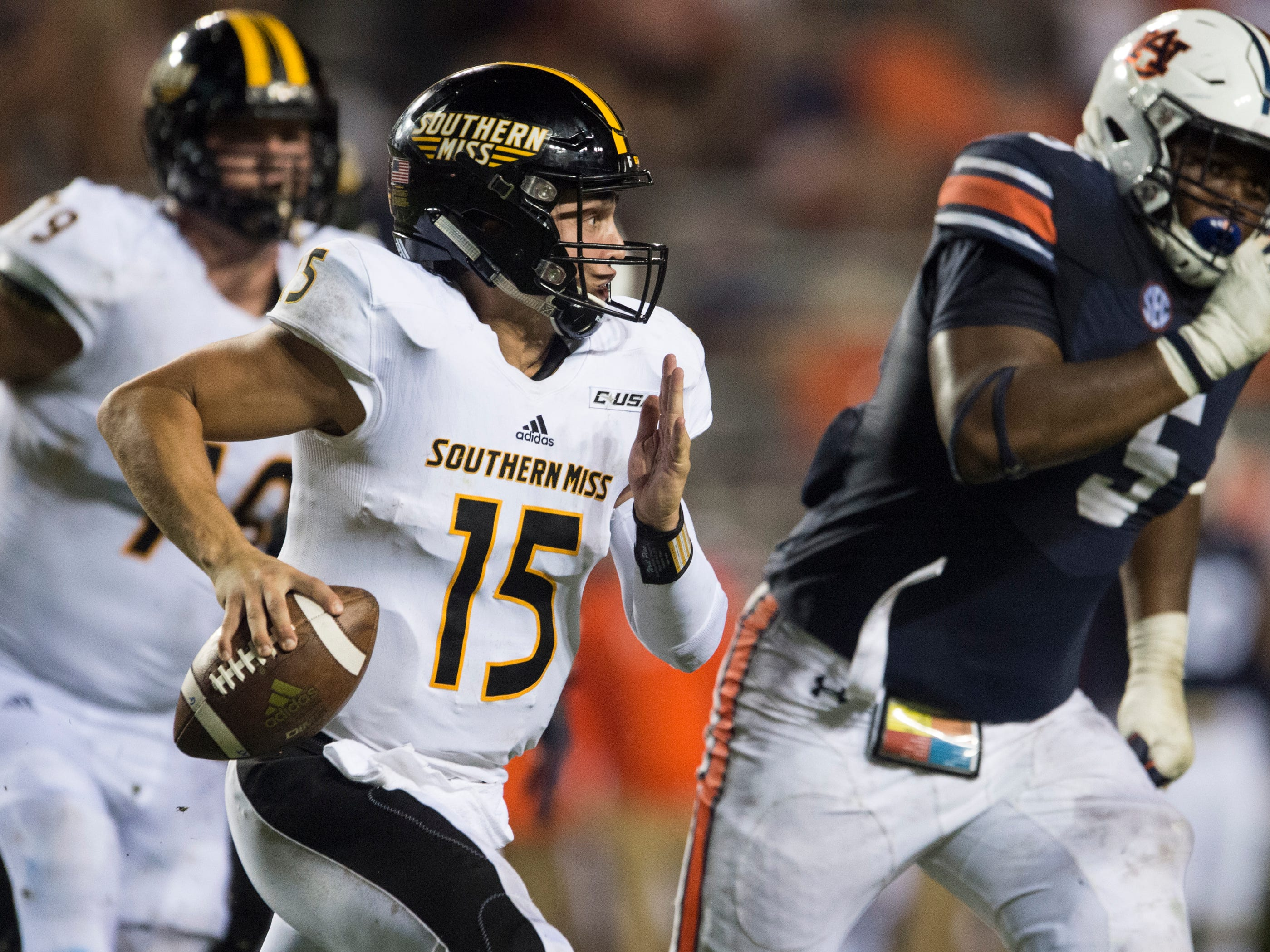 Southern Miss' Jack Abraham (15) scrambles out of the pocket pressured by Auburn's Derrick Brown (5) at Jordan-Hare Stadium in Auburn, Ala., on Saturday, Sept. 29, 2018. Auburn defeated  Southern Miss 24-13.