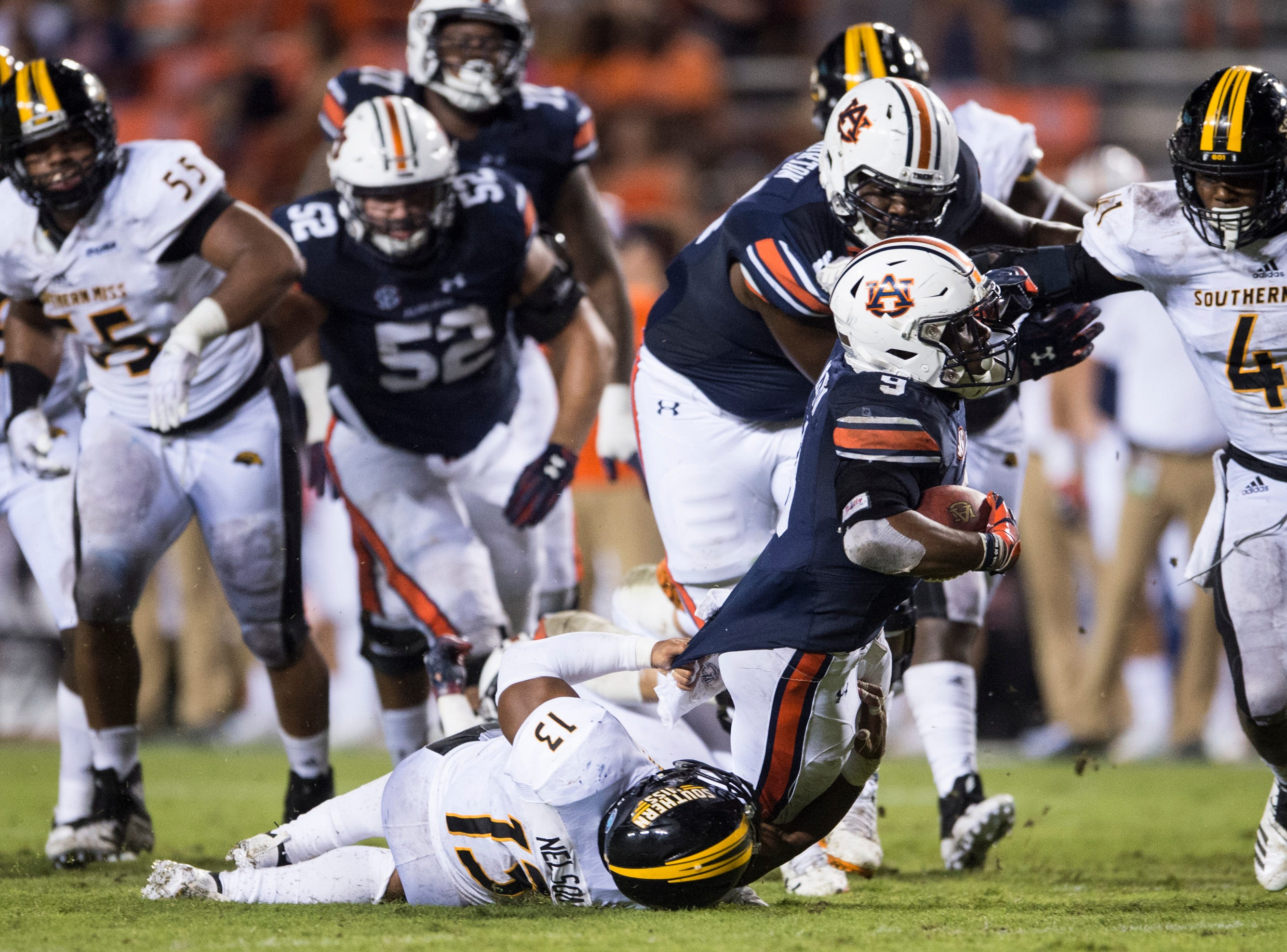 Auburn's Kam Martin (9) is dragged down by Southern Miss' Picasso Nelson Jr. (13) at Jordan-Hare Stadium in Auburn, Ala., on Saturday, Sept. 29, 2018. Auburn defeated  Southern Miss 24-13.