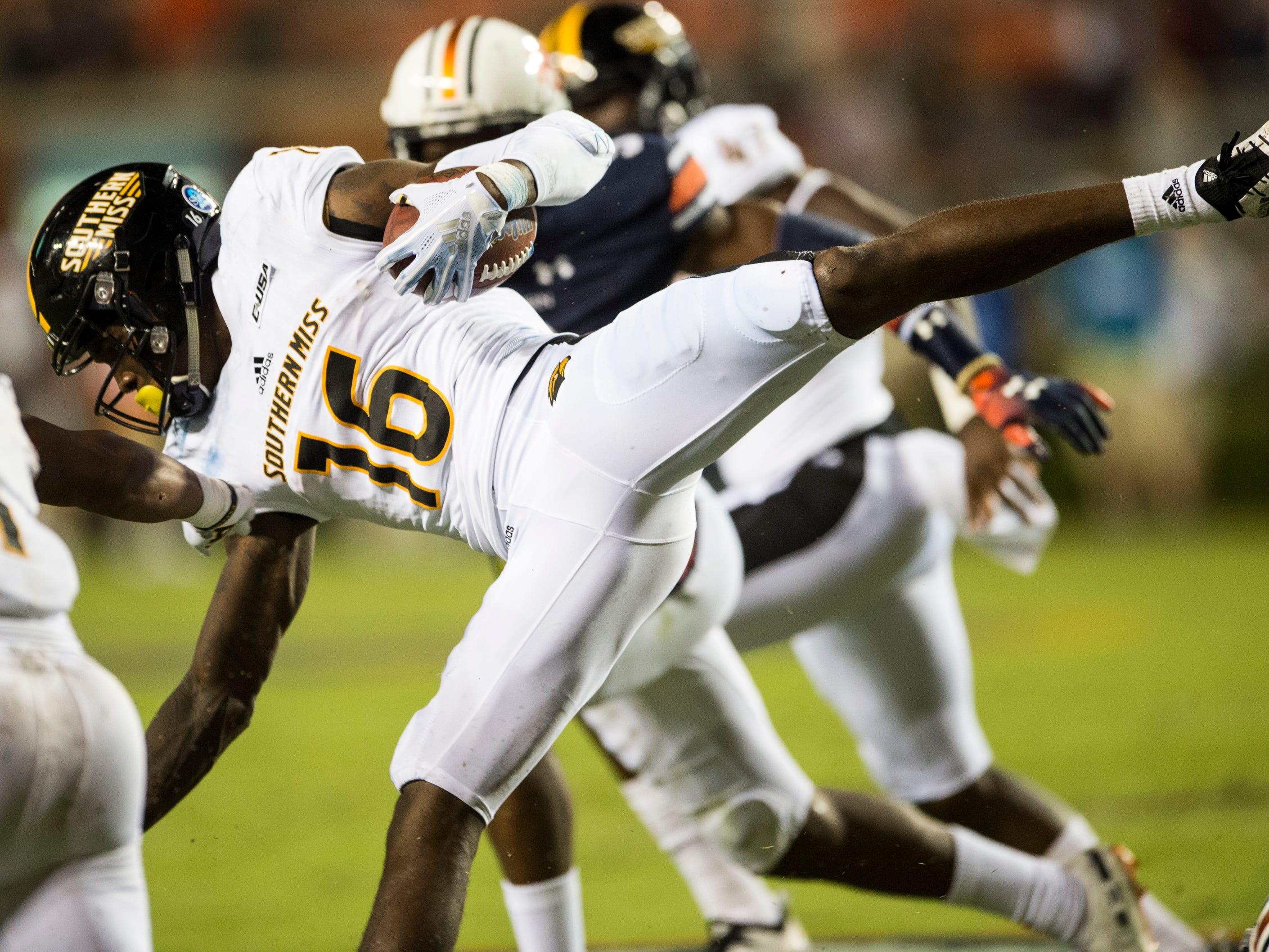 Southern Miss' Quez Watkins (16) trips over an Auburn defender as he runs the ball at Jordan-Hare Stadium in Auburn, Ala., on Saturday, Sept. 29, 2018. Auburn defeated  Southern Miss 24-13.