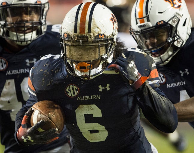 Auburn's Christian Tutt (6) tries to clean his face mask after getting tackled in the mud after returning an interception against Southern Miss at Jordan-Hare Stadium in Auburn, Ala., on Saturday, Sept. 29, 2018. Auburn defeated  Southern Miss 24-13.