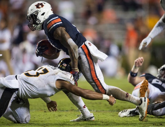 Auburn's Kam Martin (9) is tackled by Southern Miss' Picasso Nelson Jr. (13) at Jordan-Hare Stadium in Auburn, Ala., on Saturday, Sept. 29, 2018. Auburn defeated  Southern Miss 24-13.