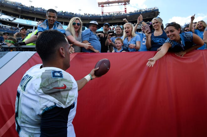 Titans quarterback Marcus Mariota (8) celebrates the overtime win with fans Sunday at Nissan Stadium.