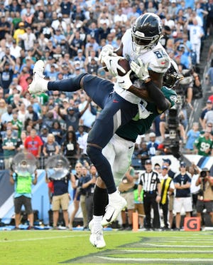Titans wide receiver Corey Davis (84) makes the game-winning touchdown catch over Eagles cornerback Avonte Maddox (29) in overtime Sunday.