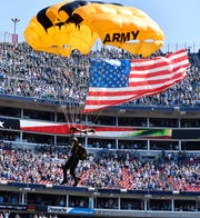 A parachutist from the U.S. Army Golden Knights enters the stadium before the game at Nissan Stadium Sunday, Sept. 30, 2018, in Nashville, Tenn.