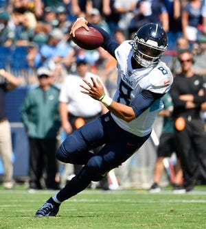 Titans quarterback Marcus Mariota (8) scrambles out of the pocket on the first possession of the game Sunday.