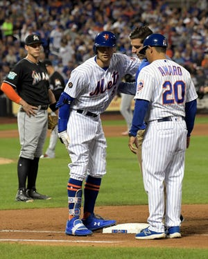 New York Mets' Brandon Nimmo (9) talks with first base coach Ruben Amaro Jr. (20) and a trainer after getting injured running out a single during the seventh inning of a baseball game as Miami Marlins first baseman Peter O'Brien, left, looks on Saturday, Sept. 29, 2018, in New York.