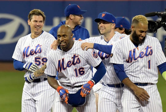 New York Mets' Jose Lobaton (59), David Wright, and Amed Rosario (1) congratulate Austin Jackson (16) after Jackson hit a home run to defeat the Miami Marlins 1-0 during the 13th inning of a baseball game Saturday, Sept. 29, 2018, in New York.