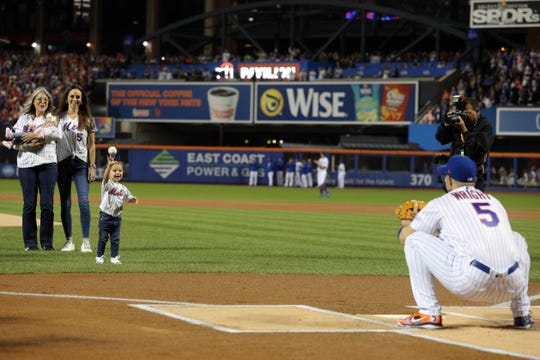 Sep 29, 2018; New York City, NY, USA; New York Mets third baseman David Wright (5) catches his daughter Olivia's ceremonial first pitch before a game against the Miami Marlins at Citi Field.