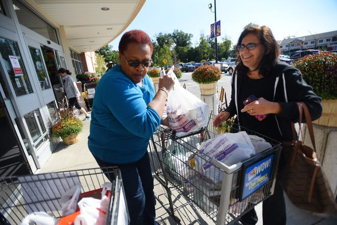 Juanita Hamilton (L) of Paterson who works for CUMAC, receives a bag of food from Wyckoff resident (who declined to give her name) during a Food Drive at Stop & Shop in Wyckoff on 09/30/18.This is The RecordÕs 27th year supporting the Food Drive, which it founded based on reading one its own published articles about a local pantry with bare shelves.