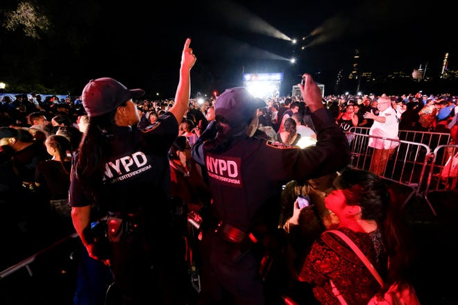 New York City Police officers direct concert goers after a barricade went down at the 2018 Global Citizen Festival in Central Park on Saturday, Sept. 29, 2018, in New York. Authorities quickly assured the crowd they were safe after the barrier fell Saturday evening. (Photo by Evan Agostini/Invision/AP)