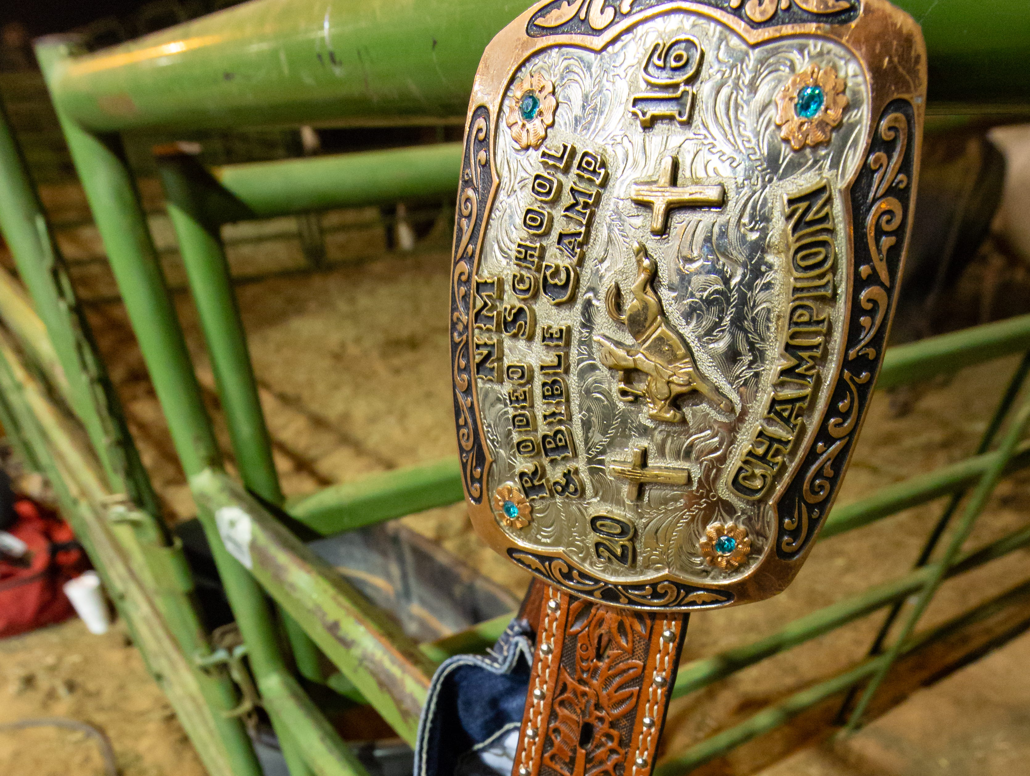 A belt buckle from the New Mexico Rodeo School & Bible Camp champion is pictured holding a pair of paints on the corral fencing in the Pete V. Domenici Arena on Saturday, Sept. 29, 2018, during the Southern New Mexico State Fair & Rodeo at the Southern New Mexico State Fairgrounds.