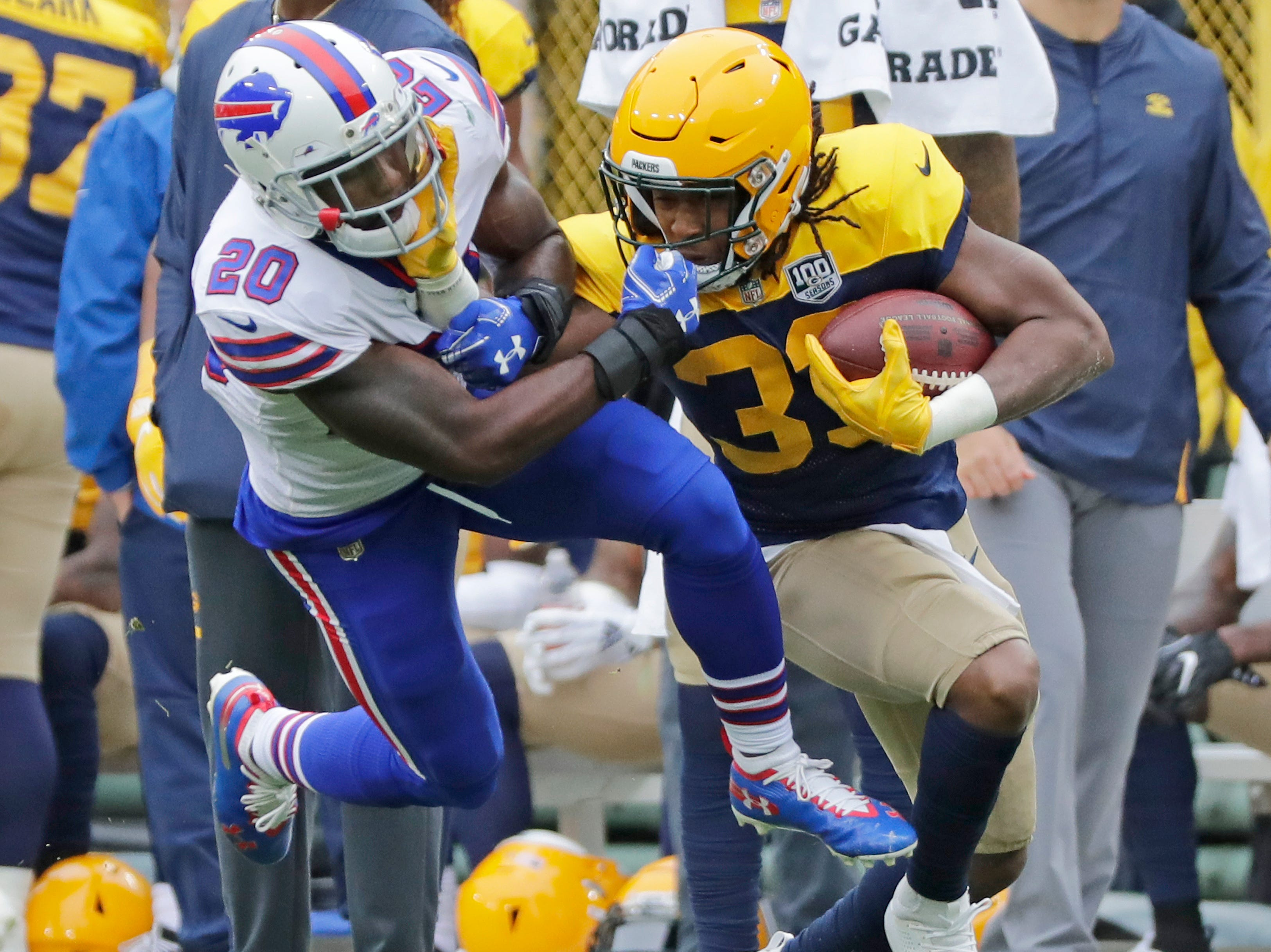 Green Bay Packers running back Aaron Jones (33) stiff arms Buffalo Bills defensive back Rafael Bush (20) in the first quarter at Lambeau Field on Sunday, September 30, 2018 in Green Bay, Wis.