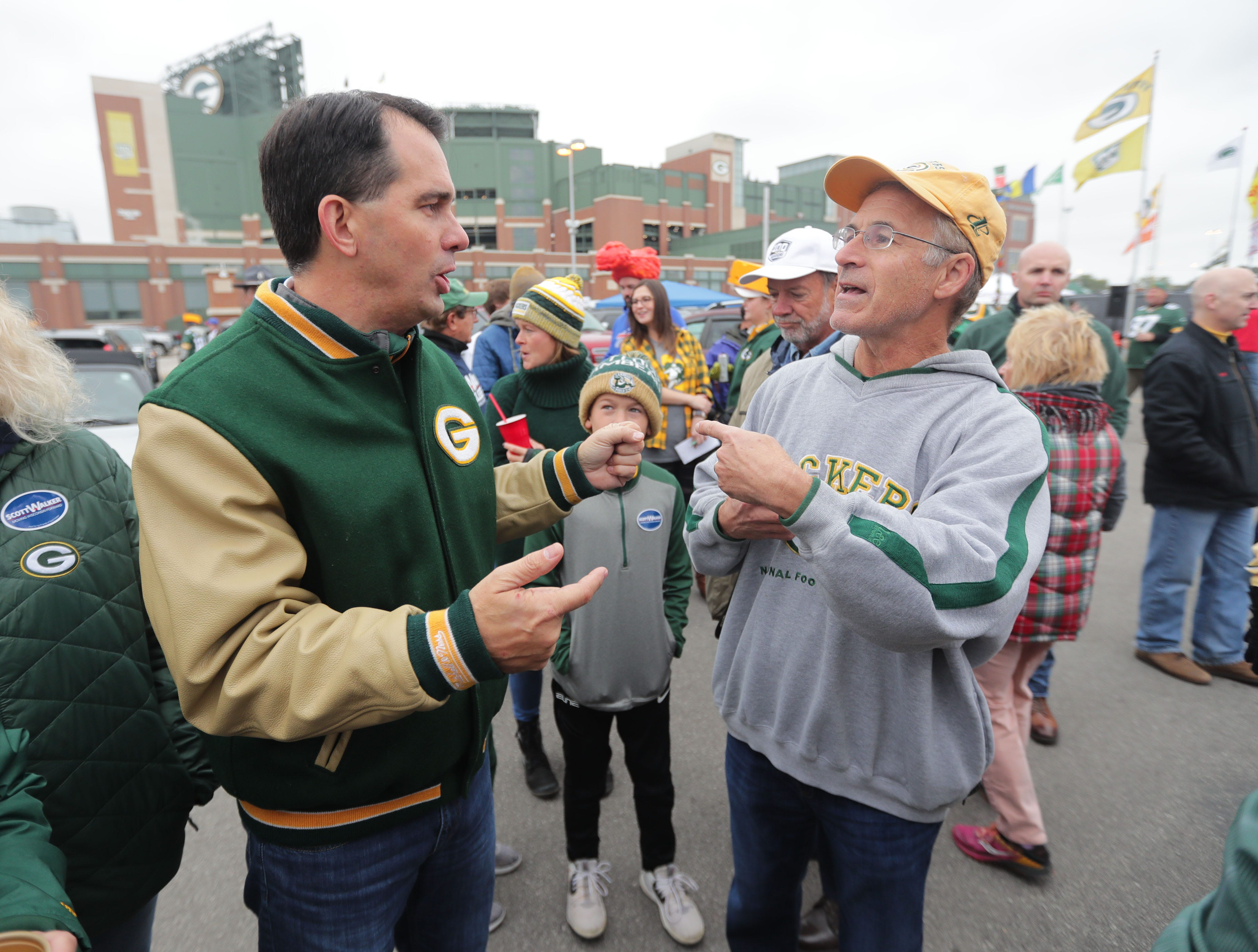 Gov. Scott Walker talks with Terrill Klett, of Atlanta before the Green Bay Packers game against the Buffalo Bills at Lambeau Field in Green Bay, Wis. on Sunday, September 30, 2018.