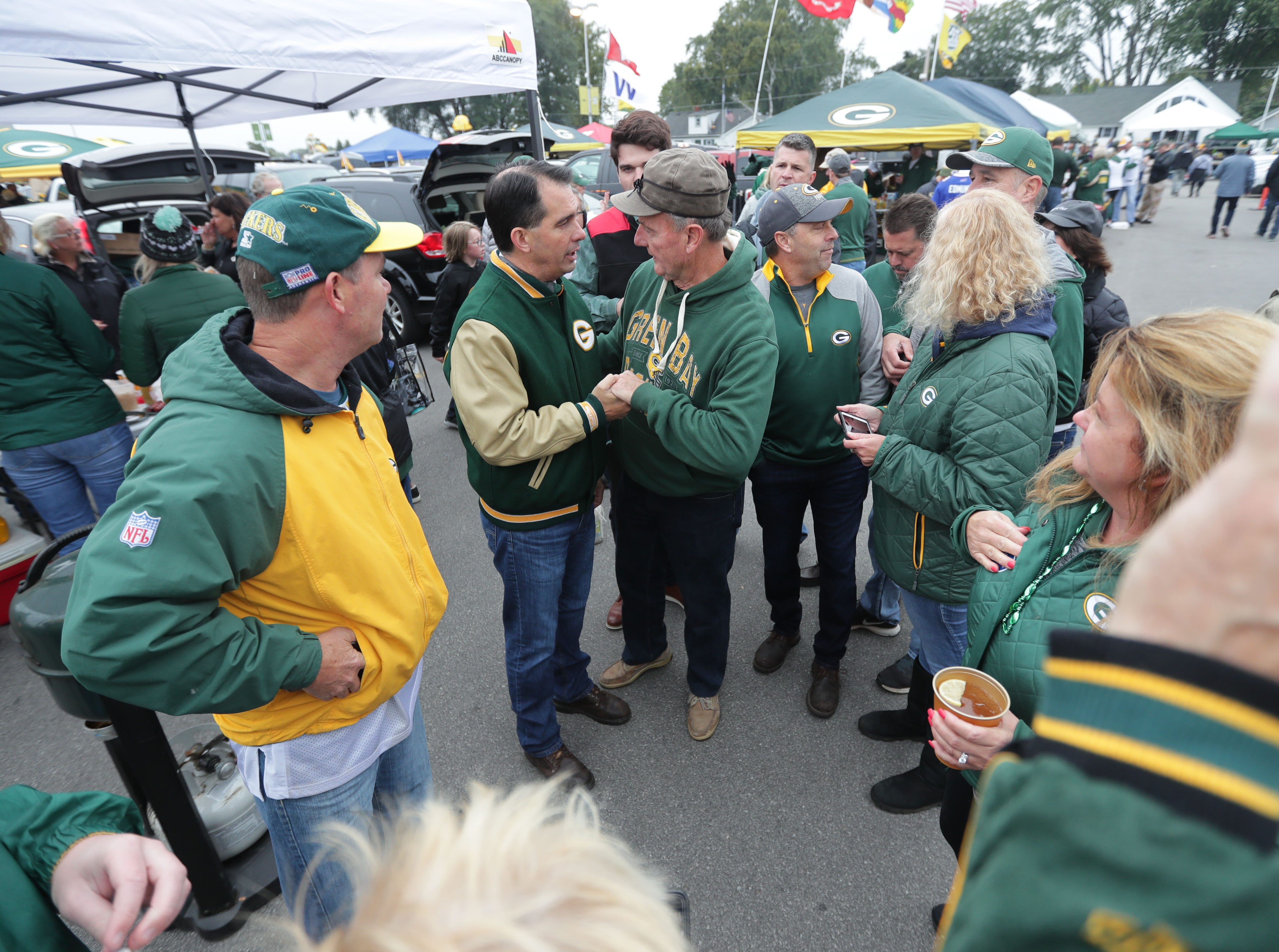 Gov. Scott Walker talks with supporters before the Green Bay Packers game against the Buffalo Bills at Lambeau Field in Green Bay, Wis. on Sunday, September 30, 2018.