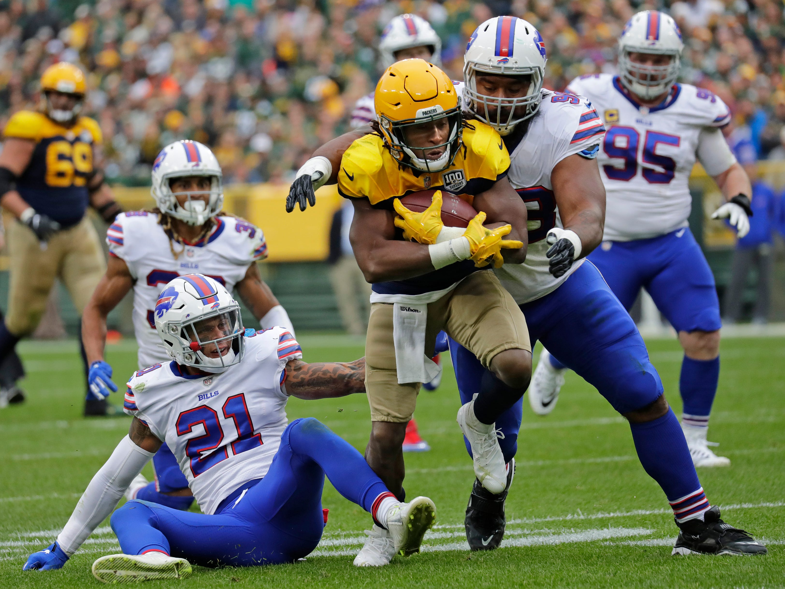 Green Bay Packers running back Aaron Jones (33) runs for a long first down against Buffalo Bills defensive back Jordan Poyer (21) and defensive tackle Star Lotulelei (98) in the second quarter during their football game Sunday, Sept. 30, 2018, at Lambeau Field in Green Bay, Wis. 