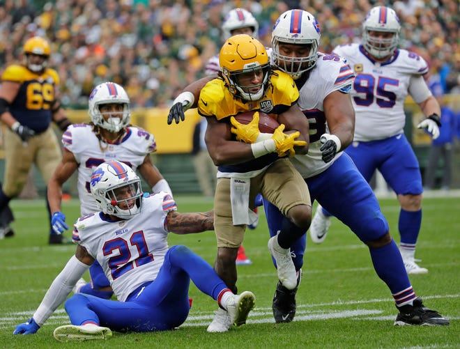 Green Bay Packers running back Aaron Jones (33) runs for a long first down against Buffalo Bills defensive back Jordan Poyer (21) and defensive tackle Star Lotulelei (98) in the second quarter during their football game Sunday, Sept. 30, 2018, at Lambeau Field in Green Bay, Wis. Dan Powers/USA TODAY NETWORK-Wisconsin