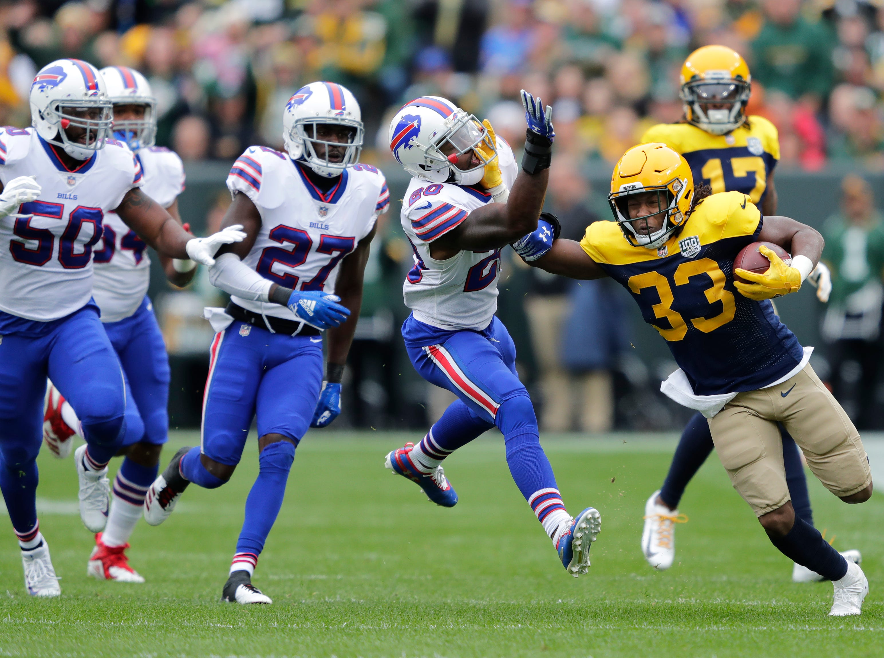 Green Bay Packers running back Aaron Jones (33) stiff arms Buffalo Bills defensive back Rafael Bush (20) on a long first down run in the first quarter during their football game Sunday, Sept. 30, 2018, at Lambeau Field in Green Bay, Wis. 